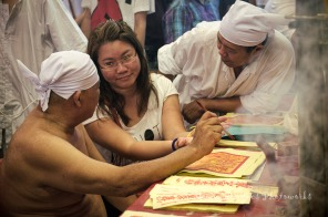 Devotees interested in getting spiritual enlightment/advice may consult the gods via a temple priest who after performing a ritual, becomes a medium to the gods. The smiling girl probably heard something funny or agreeable from the gods.