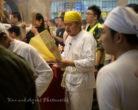 A temple priest and his entourage going round to the respective gods' altars reciting verses from a holy scripture during one of many prayer ceremonies conducted throughout the festival.