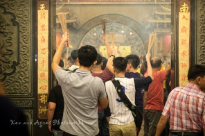 Devotees queuing at the main entrance to proceed to the temple's prayer halls. Note how the devotees clutch and hold the bundle of joss sticks high, out of harm's way.